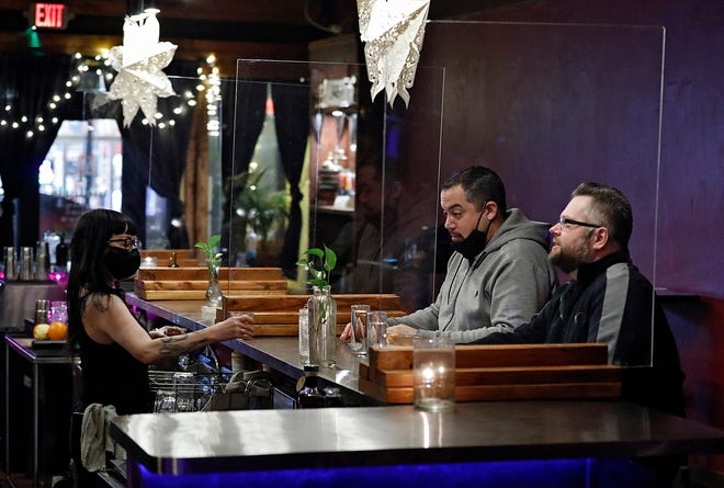 Bartender Shea Bainbridge serve drinks to Lyle Bigelow, back right, and Alex Kiss, front right, on Feb. 3 at Two Truths bar in Columbus. The bar has been busier since the statewide curfew was pushed back to 11 p.m.