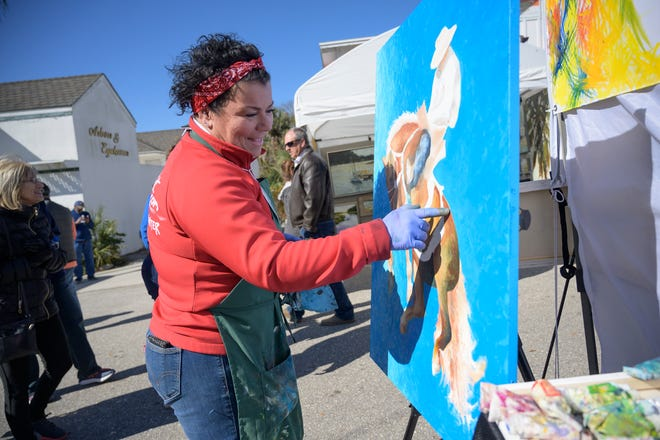 An artist demonstrates her painting at the 45th annual Mount Dora Arts Festival on Sunday, Feb. 2, 2020.