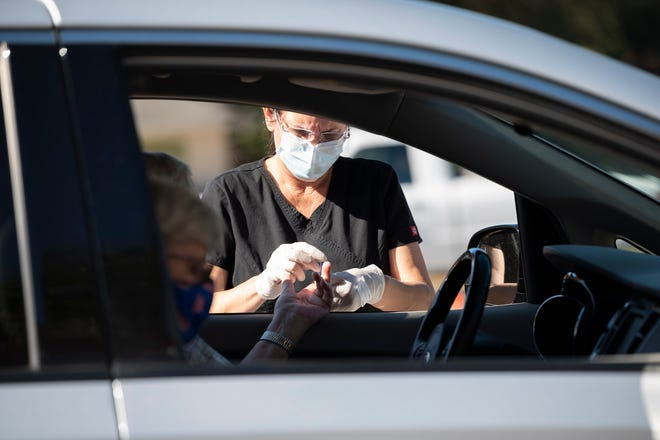 A health care worker conducts a rapid test for COVID-19 at the Lake Square Mall in Leesburg. [Cindy Peterson/Correspondent]