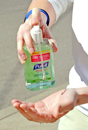 Applying Purell hand sanitizer by GOJO.  Mike Schenk, The-Daily-Record.com