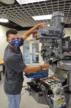 Wayne County Schools Career Center student Dominick Kreger of Triway changes atool on a milling machine in Machining Technologies. The Career Center is holding an open house Feb. 16 and 18 for prospective students.