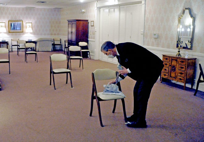 Funeral director Mitch Sleek of McIntire, Bradham and Sleek Funeral Home in Wooster disinfects the socially distanced chairs before the next service.