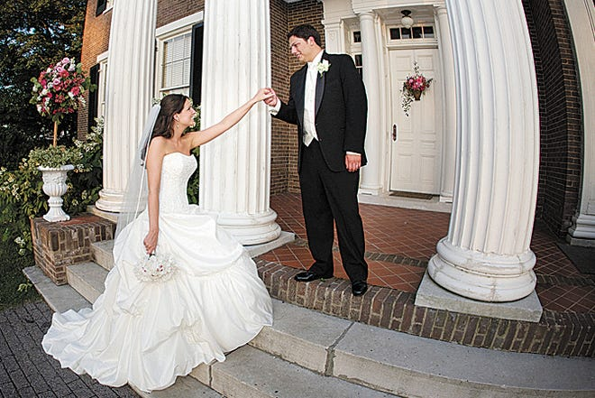 A couple celebrates their wedding day on the steps of the Rippaavilla Plantation.