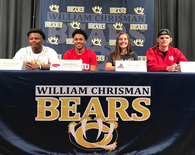 Two members of the William Chrisman High School football team and two Bears tennis players signed letters of intent Wednesday at the high school. Monterio McAfee, from left, signed with Vermillion Community College, Jayden Woods with MidAmerica Nazarene University to play football. Tennis players Krystal Olson, who signed with Midland University and Jordan Twenter, who signed with Bethel College, were moved to tears by comments from their coach, Jason Grubb.