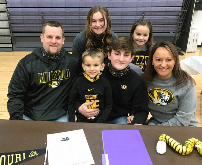 Korbin Shepherd, an undefeated 132-pound wrestler and state champion at Blue Springs High School, is joined by his family - from left, dad Brandon, brother Kyler, sister Kadence, sister Kennedi and mom Heather - at his signing ceremony inside the school gym Wednesday afternoon. He signed his letter of intent with sixth-ranked Missouri.