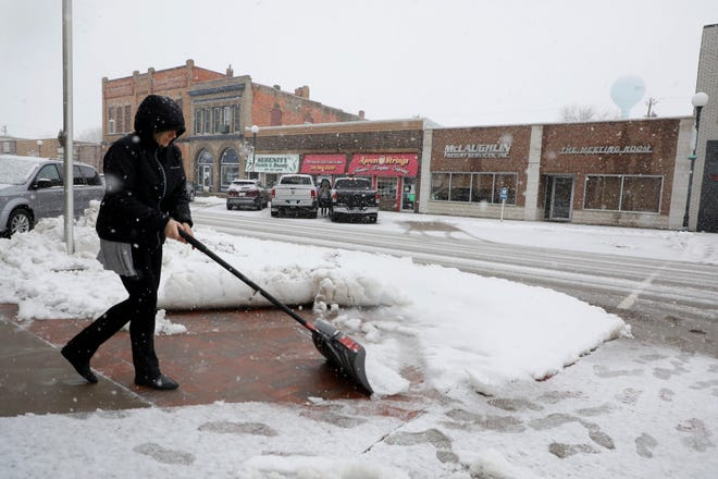 Sandra Janssen, a loan officer at the Mediapolis Savings Bank, shovels the sidewalk in front of the bank Thursday as heavy, wet snow falls in downtown Mediapolis. Portions of southeast Iowa were under a winter weather advisory calling for slippery road conditions and areas of blowing snow that would significantly reduce visibility.