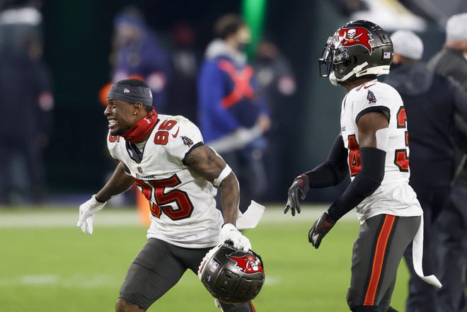 Tampa Bay Buccaneers' Jaydon Mickens (85) reacts with Javon Hagan after winning the NFC championship NFL football game against the Green Bay Packers in Green Bay, Wis., Sunday, Jan. 24, 2021. The Buccaneers defeated the Packers 31-26 to advance to the Super Bowl. (AP Photo/Jeffrey Phelps)