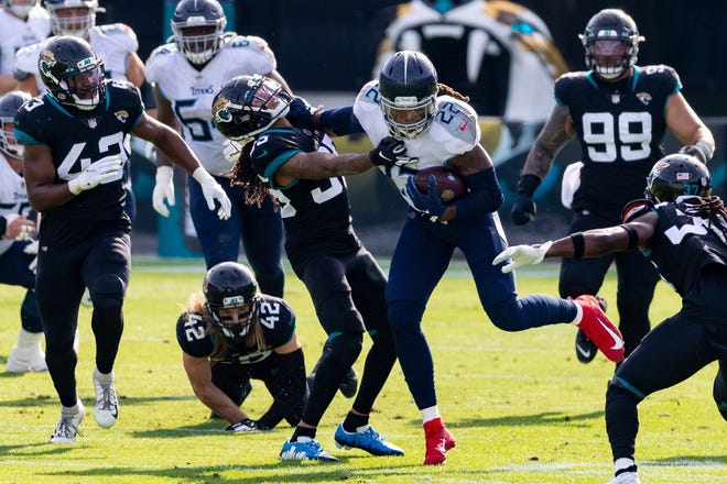 Titans running back Derrick Henry (22) stiff-arms Jaguars cornerback Sidney Jones (35) during a December game. The Yulee High School graduate was named NFL Offensive Player of the Year.
