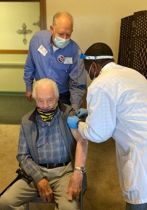 Harold Reid, 100, was the first to  get a COVID-19 vaccine shot at Newton Presbyterian Manor from a Walgreens staffer with the assistance of Marc Kessinger, executive director.
