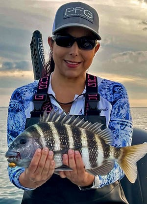 Marianne Carr, of Lakeland, shows of a keeper size 18-inch sheepshead she caught on a live shrimp while fishing in lower Tampa Bay with Capt. Daryll Patisaul of Flat Satisfied Fishing Charters of Ruskin last weekend.
