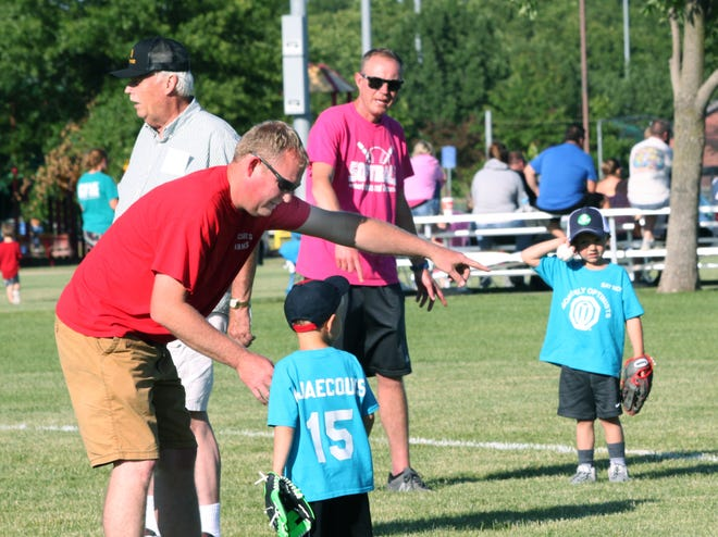 A volunteer coach with the Moberly Optimist Club's summer youth tee-ball program gives instruction to one of his players during a league game played at the Howard Hils Athletic Complex.