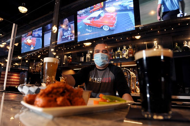 Bartender Josue Rosa, with chicken wings and beer, is ready to serve up a Super Bowl experience at SKYBOKX 109 Sports Bar and Grill in Natick, Feb. 4, 2021.