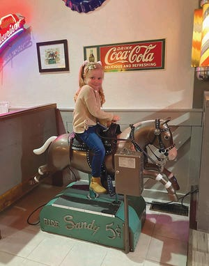Five-year-old Tenley Kirby of Pratt, enjoys a ride on Sandy, the old rocking horse, at The Chapeau, 701 North Main in Pratt.  Sandy has been giving nickel rides at The Chapeau restaurant for two decades after being purchased at auction by Chapeau owner Vince Epp.  She was formerly located at the North Dillons in Pratt.
