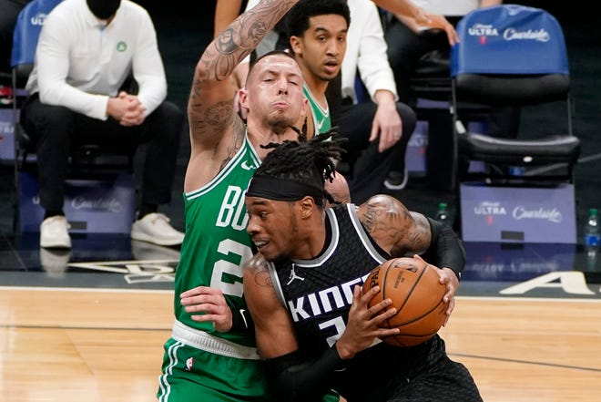 Kings center Richaun Holmes goes to the basket against Celtics center Daniel Theis during the first quarter Wednesday night in Sacramento.