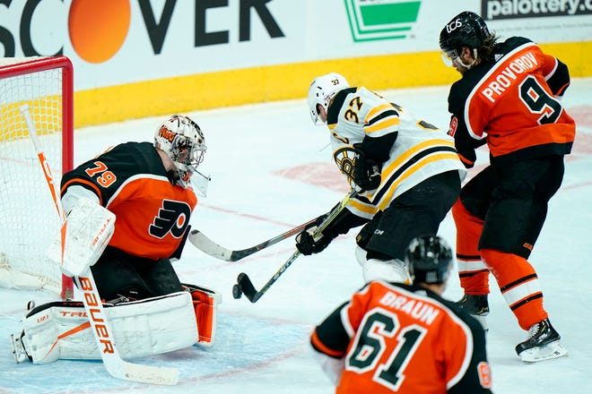 The Bruins' Patrice Bergeron sends the game-winning goal past the Flyers' Carter Hart during overtime Wednesday night in Philadelphia.