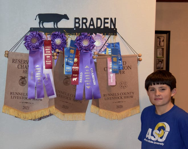 Braden Hoppe stands beside some of the awards that he's won throughout his 4-H participation. Hoppe and his family participate in about 11 shows and jackpots every year.