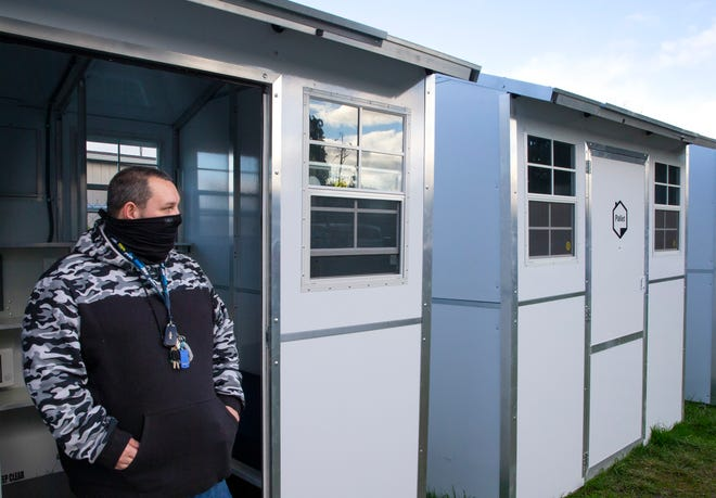 St. Vincent de Paul of Lane County staff member Jonah McMillin stands in the doorway of one of the Pallet shelters set up along Highway 99 to provide a place for patients from PeaceHealth to recuperate after a visit to the hospital.