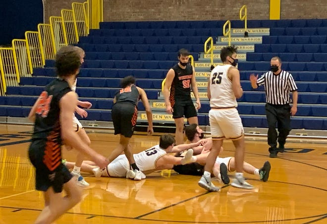 Winnebago and Sterling players scramble for a loose ball during the season opener on Wednesday, Feb. 3, 2021, in Sterling. The Golden Warriors held off a second-half Indians rally for a 71-59 win.