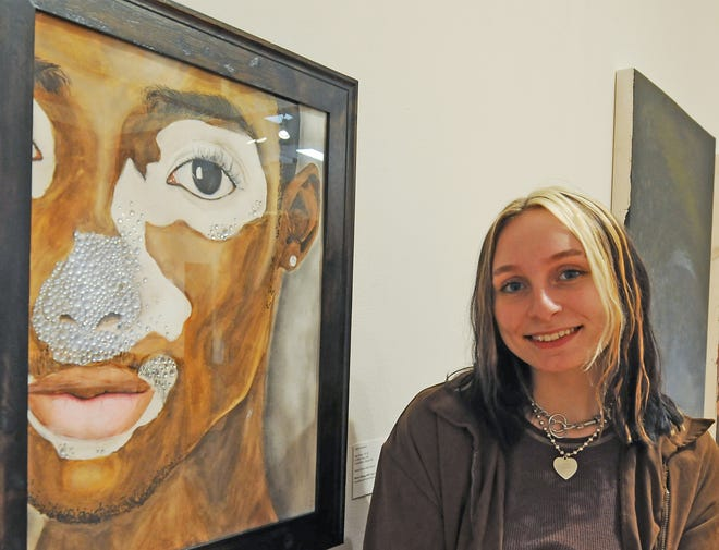 """Salina Central art student Layna Kinnaird smiles next to her gouache that contains Swarovski crystals titled """"What's Wrong With Your Skin?"""" that was selected to be part of the 2021 Sunflower Biennial exhibition opening this week at the Salina Art Center."""