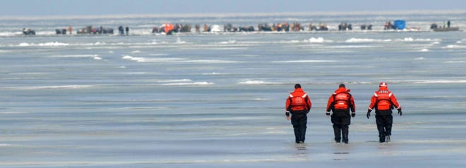 U.S. Coast Guard crewmen walk across frozen Lake Erie near Crane Creek State Park in Oak Harbor, Ohio, as they attempt to reach more than 100 fishermen on Feb. 7, 2009. A miles-wide ice floe broke away from Lake Erie's shoreline, trapping the fishermen, some for as long as four hours. One person fell into the water and later died.