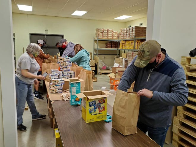 Project Topeka volunteers fill bags with food that will be given to students at local elementary schools.