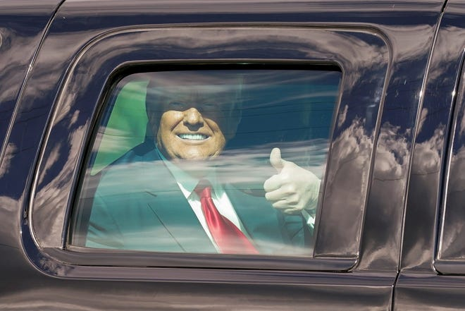 President Donald Trump gestures to supporters en route to his Mar-a-Lago Florida resort on Jan. 20  in West Palm Beach, Fla.