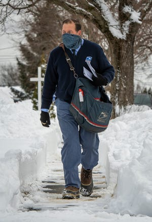 U.S. Postal Service mail carrier Paul Duquette walks his route on Ascadilla Road in Worcester.