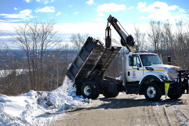 WORCESTER — A DPW worker unloads his dump truck full of snow at the property off Goddard Memorial on Thursday, which also happens to have a stellar view of downtown.