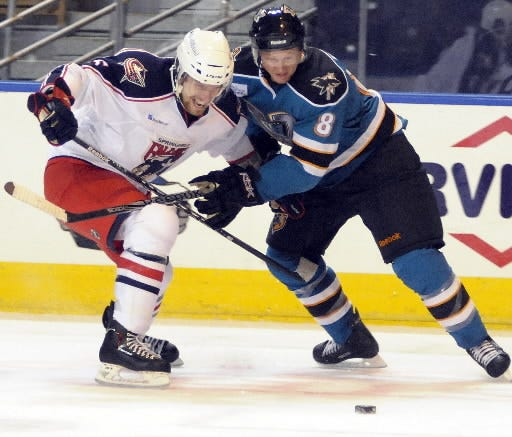 Worcester Sharks defenseman Mike Moore, right, keeps the Springfield Falcons' Jon Sigalet off the puck during a game in 2010.