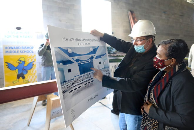 "Architect Paul Stresing talks about the design of the stage and cafeteria with Donna Jones, the deputy superintendent of Alachua County Public Schools, during the ""Topping Out"" ceremony of the renovation of Howard Bishop Middle School, on Thursday in Gainesville."