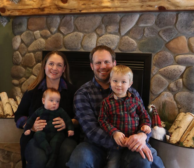 Rose and Brian Tipka sit with two of their children, Benjamin, 3 months, and Dillon, 3 years, at the living room fireplace in Mount Pleasant Lodge. (TimesReporter.com / Jim Cummings)