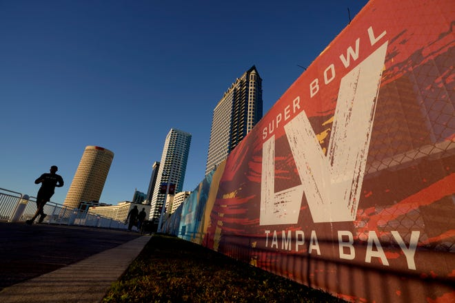 A man passes signage for Super Bowl 55 as he runs along the Hillsborough River on Wednesday, Feb. 3, 2021, in Tampa, Fla. The city is hosting Sunday's Super Bowl football game between the Tampa Bay Buccaneers and the Kansas City Chiefs.