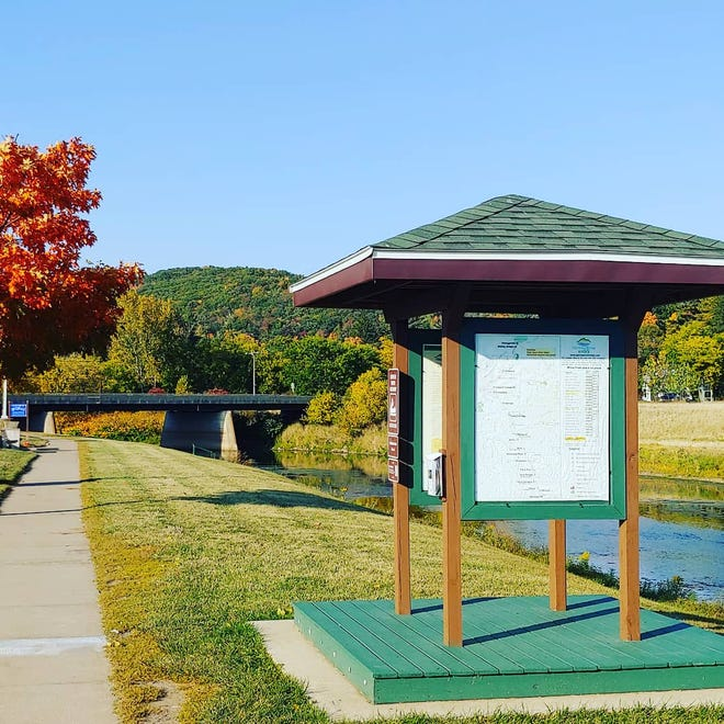 The Genesee River travels through Wellsville. At left is the Riverwalk trail with a Genesee River Wilds kayaking access kiosk at right.