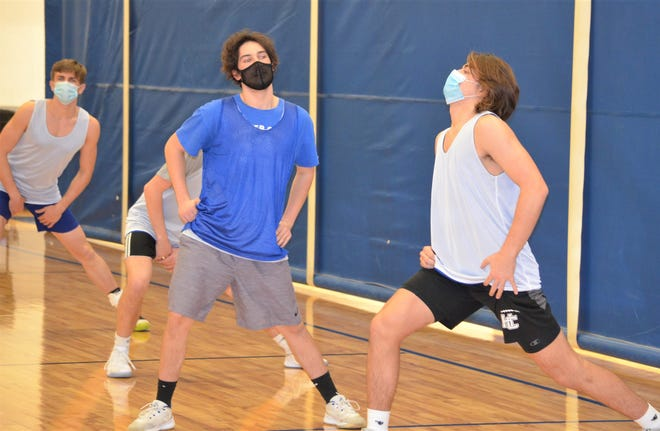 Harper Creek's Ben Shafer, right, and Zane Bowling, go through stretches at practice as it was announced Thursday that the basketball season will be allowed to resume on Monday.