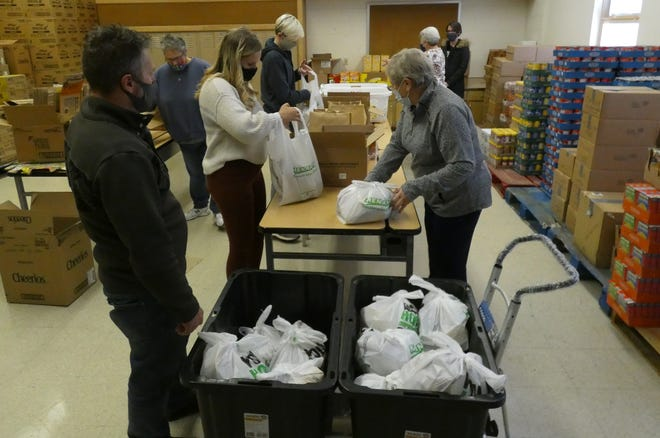 Bucyrus Backpack Program volunteers pack food for Crestline and Buckeye Central students on Wednesday in Bucyrus City Schools' Lincoln Administration Building on Wednesday afternoon.