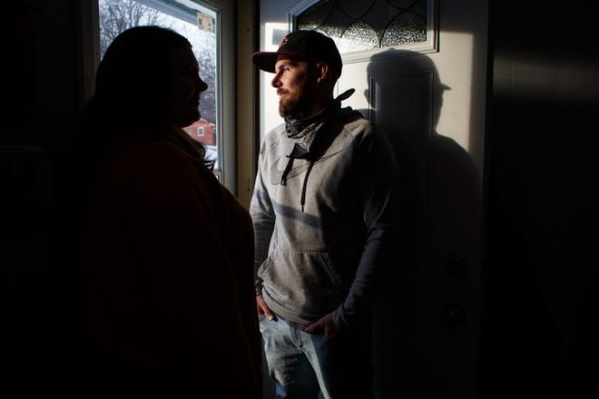 """James Taylor, 34, right, and his fiancé, Alison Sharp, 40, left, pose for a portrait by the door of their home on Wednesday, Feb. 3, 2021, in Des Moines. The couple moved out of their apartment and into the home last July and were proud of what they had accomplished through savings, """"to come so far and lose it all for something that is not even our fault would be awful,"""" Sharp said. Taylor, a concrete finisher, says he has 41 cents in his bank account and about $2,800 in bills."""