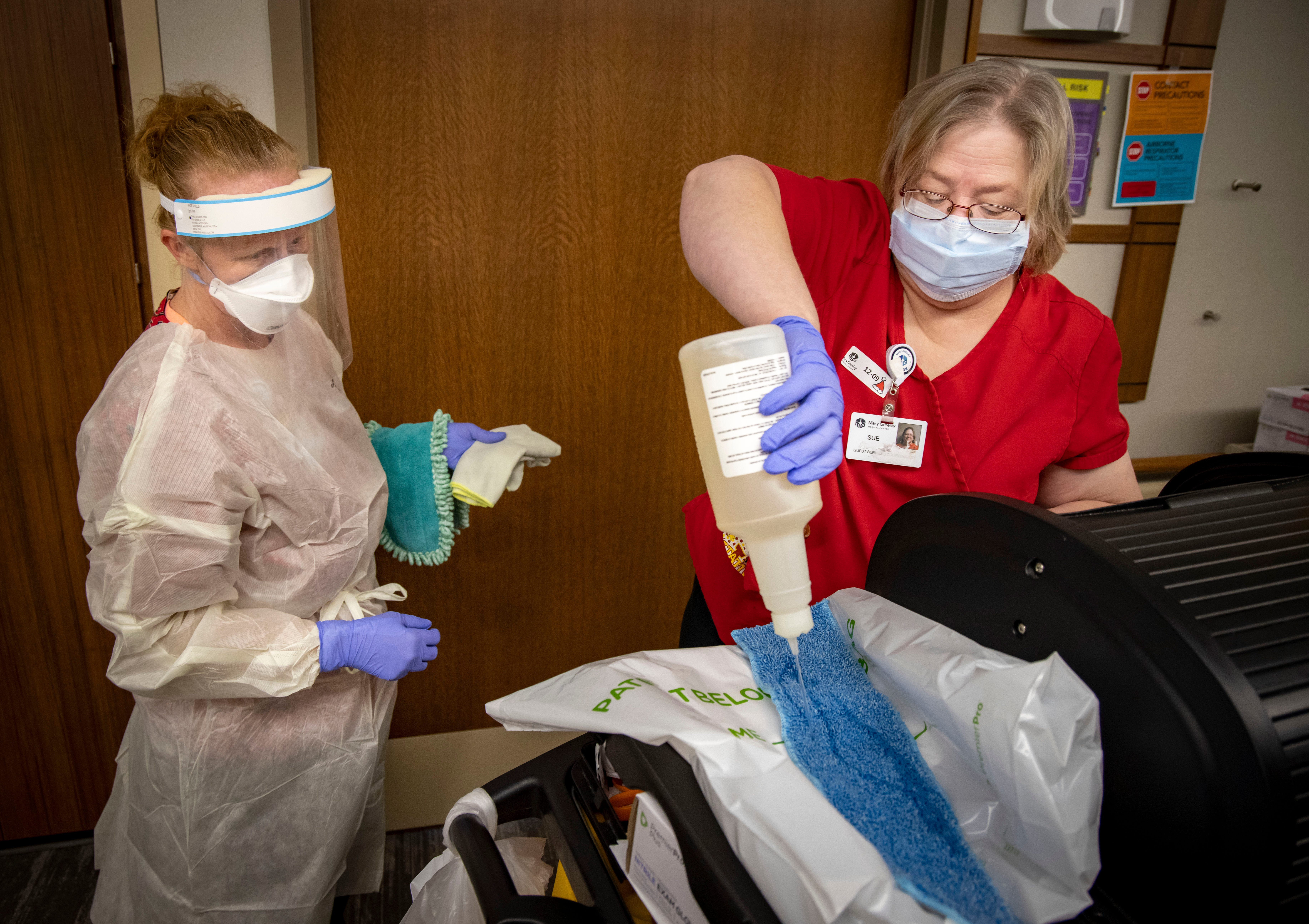 Sherry Weitzel wears full PPE as her partner Sue Walsh wets a cloth to clean a COVID-19 patient's room at Mary Greeley Medical Center in Ames on Dec. 9, 2020.