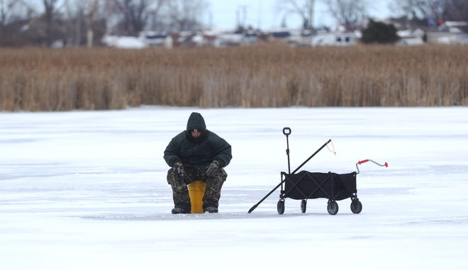 A fisherman tries to catch bluegill and perch at Metro Park in Macomb County on Wednesday, February 3, 2021.