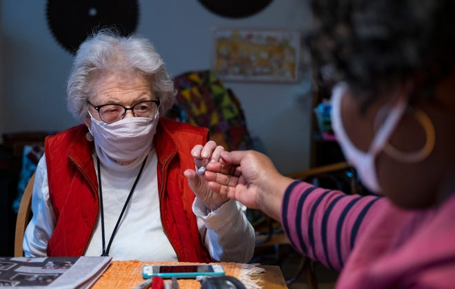 Kathryn Goldman, 89, left, is handed an adjusted hearing device from home health aide Valerie McBride-Johnson at her home in Manhattan. Experts say aging demographics and the coronavirus pandemic have exacerbated a shortage of home health workers nationwide.