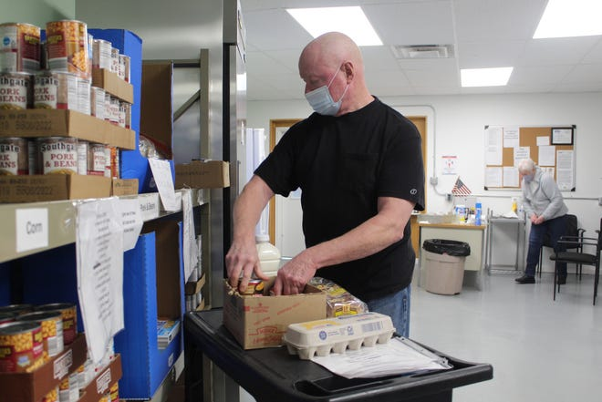 Sandusky County Food Pantry purchasing agent Larry Faist loads up a box with food for one of the county's residents Wednesday at the food pantry's Bidwell Avenue location. The food pantry has seen an increased demand since the start of the COVID-19 pandemic.