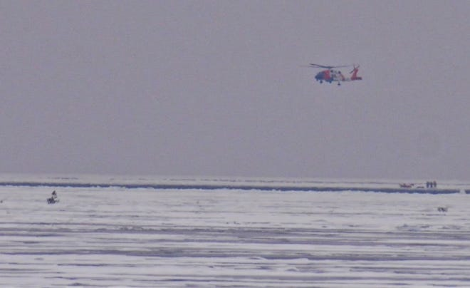 A helicopter from the Coast Guard Air Station in Traverse City, Michigan, flies in to rescue some of the 62 people stranded on ice floes that broke off from shore near Sherwood Point off Sturgeon Bay on Thursday morning.
