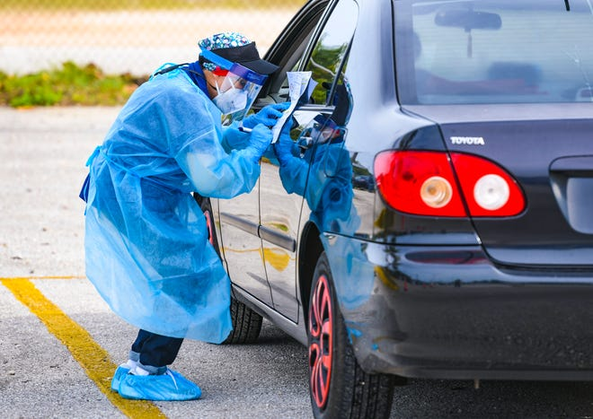Department of Public Health and Social Services nurse Eva Losbanes informs vehicle occupants of their COVID-19 test results during a drive-through outreach at the Yigo gymnasium on Thursday, Feb. 4, 2021.