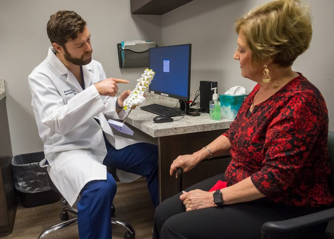 Dr. Michael McIver, left, consults with patient Sheila Venable, who suffers from chronic back pain.