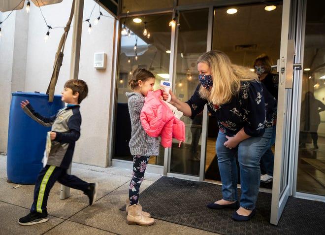 Bridget Yates, executive director of the Cornerstone Child Development Center, checks Amelia Galla's temperature upon her arrival at the St. Matthews school on Feb. 4.
