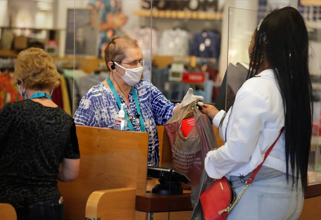 Kohl's cashier Annie Szczepanski, behind a plexiglass shield, hands a bag to a customer at the Menomonee Falls Kohl's store. The retail chain said that although sales were down in the fourth quarter, the company was seeing a gradual recovery of business.