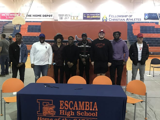 From left, Hershell Jefferson (Jamestown), Sam Allen (Tulsa), Lamont Sims (Campbellsville), Tai'shaun Key (Campbellsville), Rennie Prim Jr. (Campbellsville), Brennan Smith (Austin Peay), Tabari Taylor-Richardson (North Alabama) and Jaden Milliner (Arkansas State) sign at a ceremony at Escambia High School on Feb. 3, 2021.