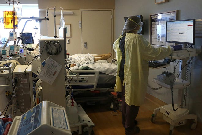 A caregiver helps a patient undergo dialysis in the Intensive Care Unit devoted to COVID-19 patients at Renown Regional Medical Center in Reno, Dec. 11, 2020.