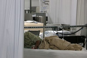 A Covid patient lies in his bed in the Alternative Care Site at Renown Regional Medical Center in Reno on Dec. 11, 2020. The ACS is located on the first floor of the Mill St. parking garage.