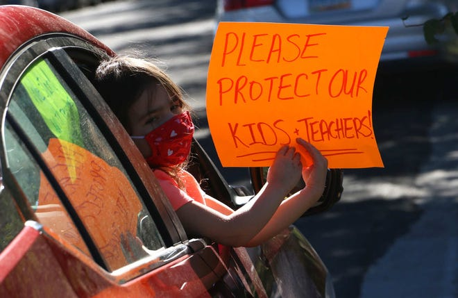 A child holds a sign as Washoe County School District teachers and supporters gather for a rally and march to protest the opening of the schools on Aug. 6, 2020.