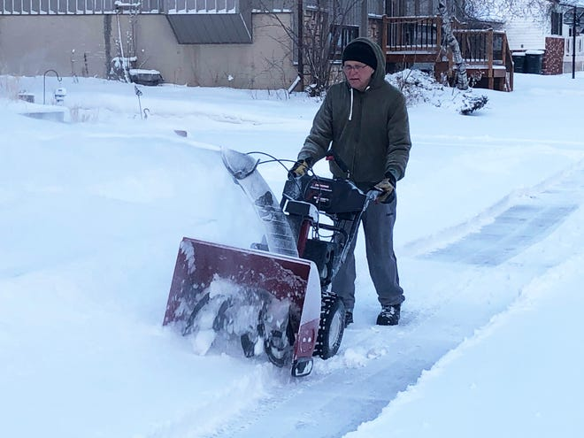 Al Graham clears his sidewalk of snow on Thursday morning in Sioux Falls.